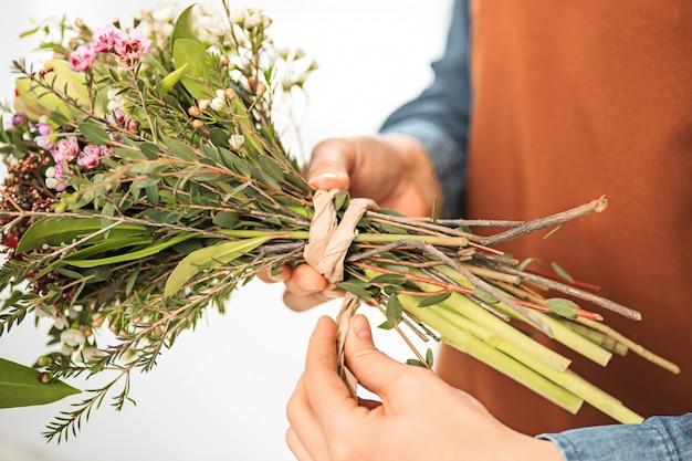 Флорист делает букет из разных цветов Бесплатные Фотографии