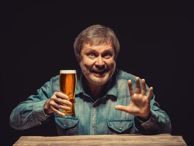 ビールのグラスとデニムシャツの男の笑みを浮かべてください。 無料写真