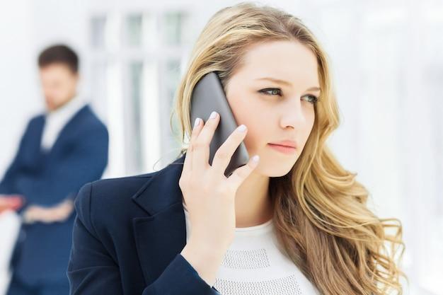 オフィスで電話で話している実業家の肖像画 無料写真