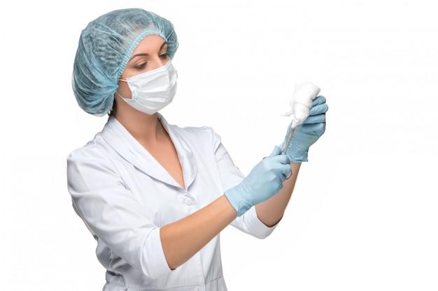 Портрет леди хирург держит хирургический инструмент на белом фоне Бесплатные Фотографии