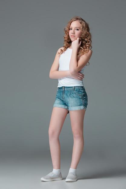 Полная длина молодой стройной девушки в джинсовых шортах на сером фоне Бесплатные Фотографии