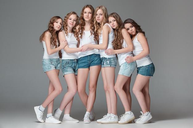 Модные девушки стояли вместе и глядя на камеру на сером фоне студии Бесплатные Фотографии