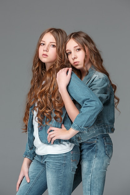 Полная длина молодой стройной девушки в джинсовых джинсах на сером фоне Бесплатные Фотографии
