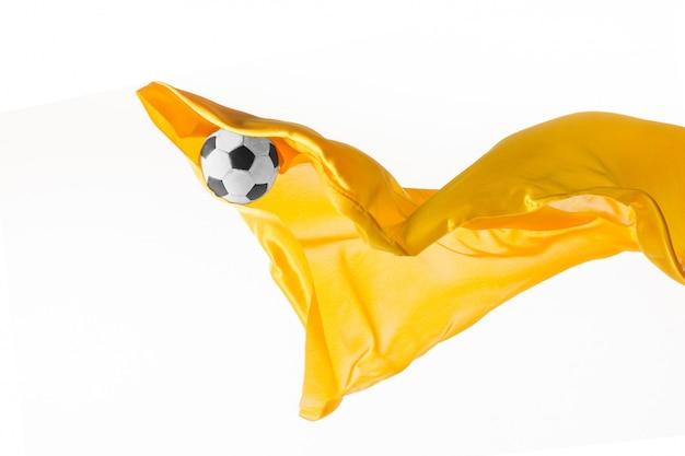 Футбольный мяч и ровная элегантная прозрачная желтая ткань изолированные или отделенные на белой предпосылке студии. Бесплатные Фотографии