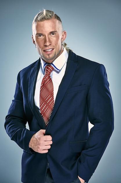 黒のスーツを着て魅力的な青年実業家の肖像画。ブロンドの髪 無料写真