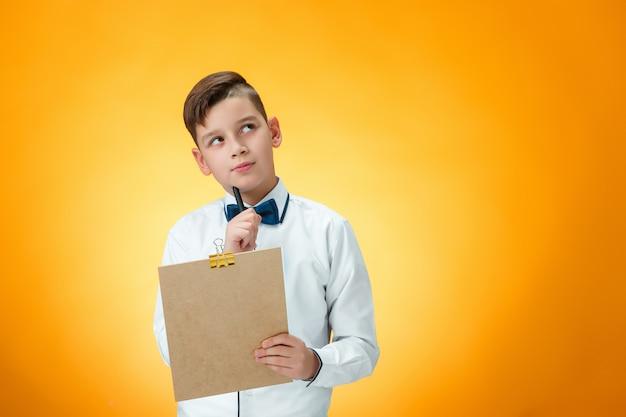 ノート用のペンとタブレットを持つ少年 無料写真