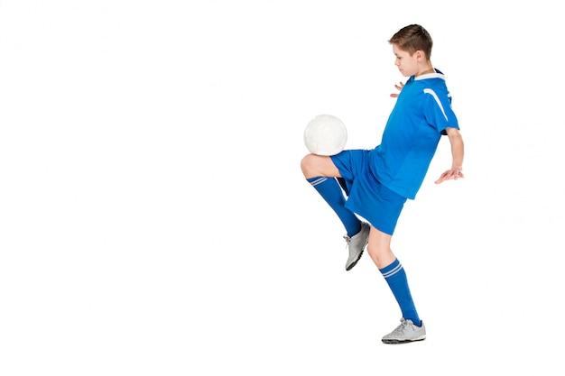 Молодой мальчик с футбольным мячом делает летающий удар Бесплатные Фотографии