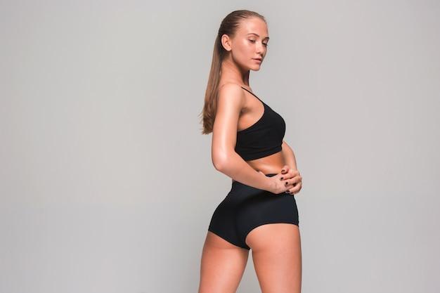 灰色の筋肉の若い女性の運動選手 無料写真