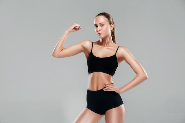 Мускулистые молодая женщина спортсменка на сером Бесплатные Фотографии