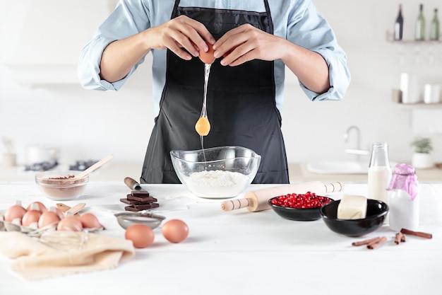 Повар с яйцами на деревенской кухне на фоне мужских рук Бесплатные Фотографии