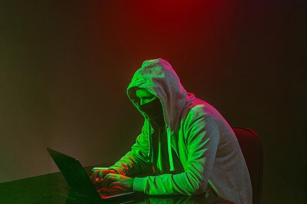 ラップトップで情報を盗むフード付きのコンピューターハッカー 無料写真
