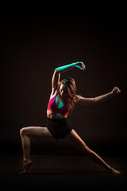 黒い壁に踊る若い美しいダンサー 無料写真