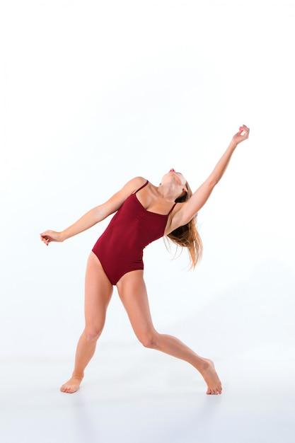 白い壁に踊るベージュのドレスの若い美しいダンサー 無料写真