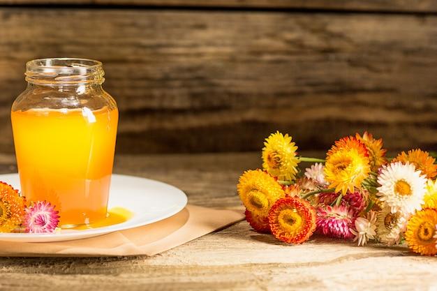 木製のテーブルの上に蜂蜜とボウル。蜂蜜の銀行は木のスプーンの近くに滞在します。 無料写真