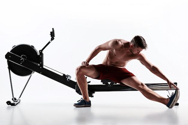 Человек, используя пресс-машина в фитнес-клубе. Бесплатные Фотографии