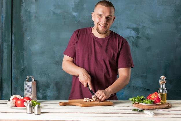 Крупным планом рука шеф-повара пекаря, делая пиццу на кухне Бесплатные Фотографии