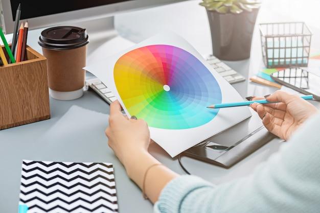 Серый письменный стол с ноутбуком, блокнотом с чистым листом, горшком с цветком, стилусом и планшетом для ретуши Бесплатные Фотографии