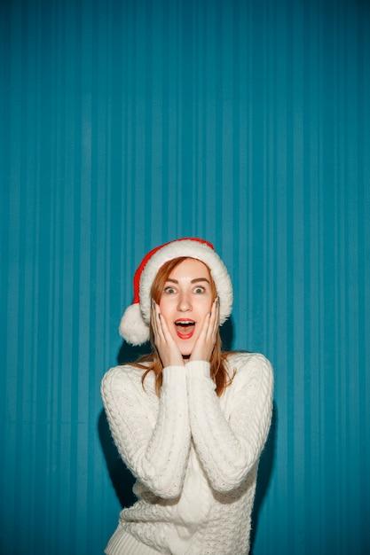 Удивленная женщина в новогодней шапке Бесплатные Фотографии