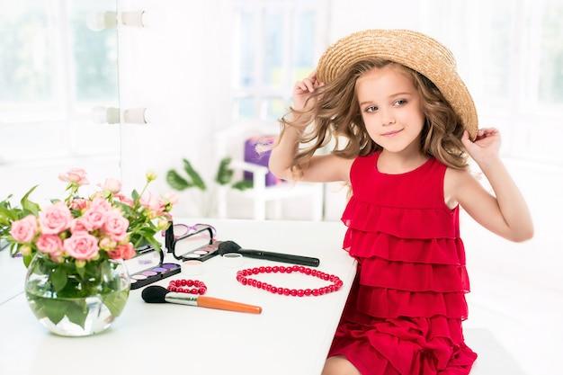 Маленькая девочка с косметикой сидит возле зеркала. Бесплатные Фотографии