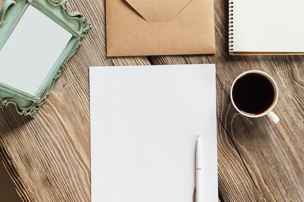Блокнот, бумага, чашка кофе и конверт с винтажной старой рамкой Бесплатные Фотографии