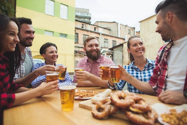 Группа друзей, наслаждаясь напитком в баре на открытом воздухе Бесплатные Фотографии