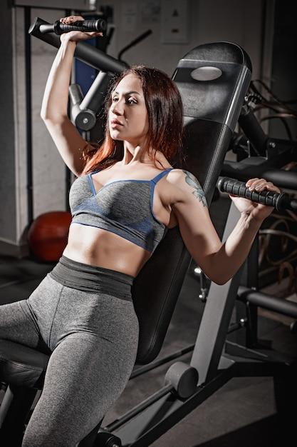 ジムでフィットネス女性重量挙げトレーニング 無料写真