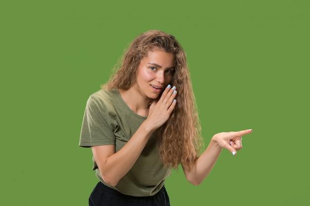 Молодая женщина шепчет секрет за ее рукой Бесплатные Фотографии