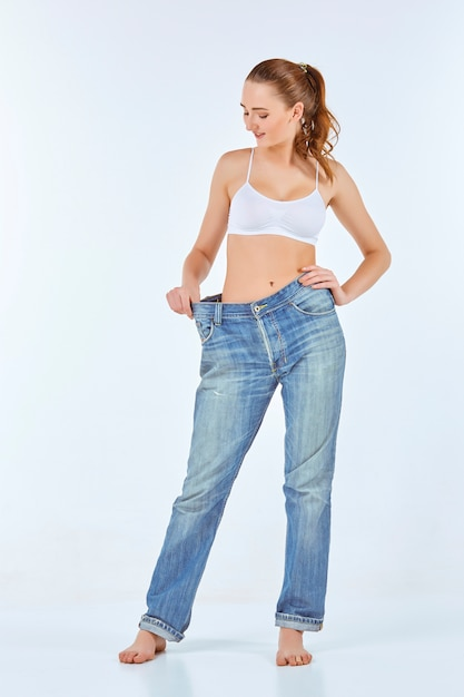 女性はスキニーになり、古いジーンズを着て 無料写真