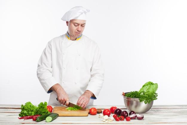 Шеф-повар готовит салат из свежих овощей на своей кухне Бесплатные Фотографии