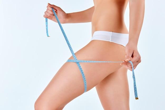 彼女の美しい体の完璧な形状を測定するメーターを保持している女性 無料写真