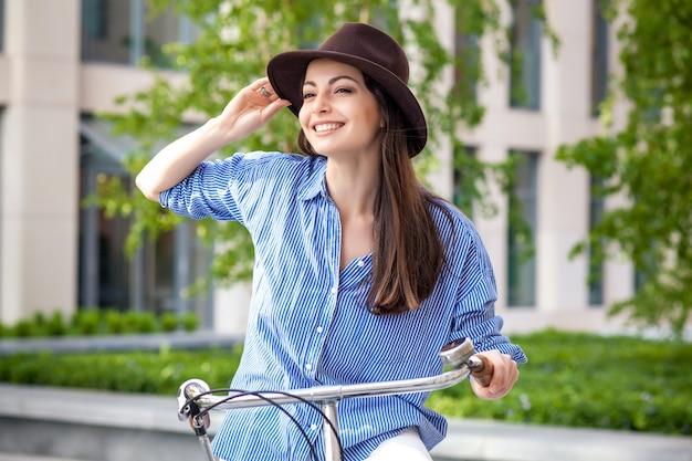 通りで自転車に乗って帽子でかわいい女の子 無料写真