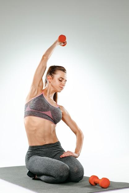 いくつかのストレッチ体操を行う美しいスリムなブルネット 無料写真