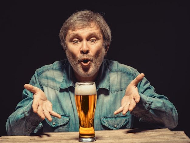 ビールのグラスとデニムシャツの魔法の男 無料写真
