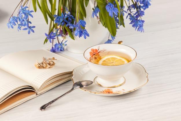 Чай с лимоном и букет синих примул на столе Бесплатные Фотографии