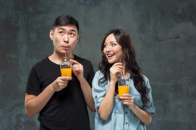 オレンジジュースのグラスを持つ若いかなりアジアカップル 無料写真