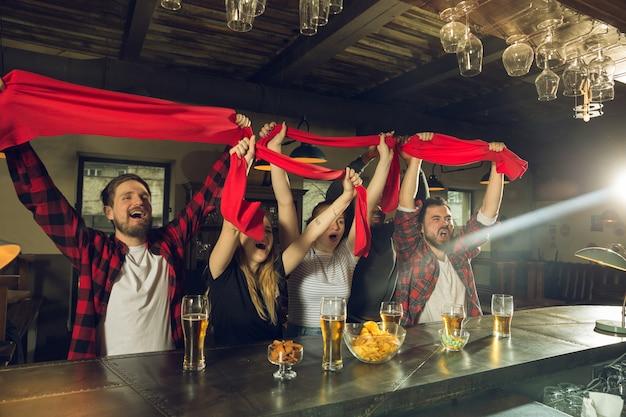 チャンピオンシップ、競争が起こっている間、スポーツファンはバー、パブで応援し、ビールを飲みます 無料写真