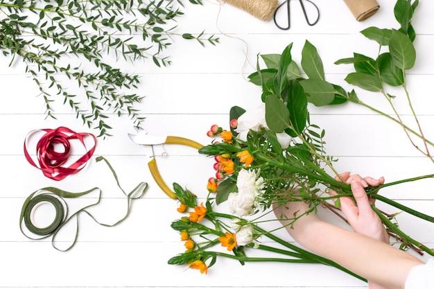 フラワーショップで美しい花束を作る女性の花屋 無料写真