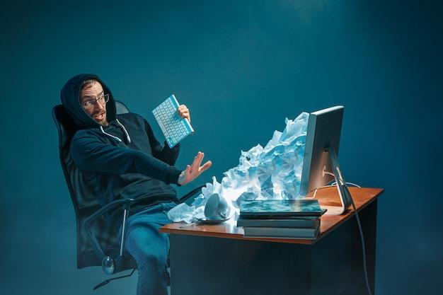若者がノートパソコンの画面で叫び、スパムに怒っている現代のオフィスの机で働いているハンサムなビジネスマンを強調 無料写真