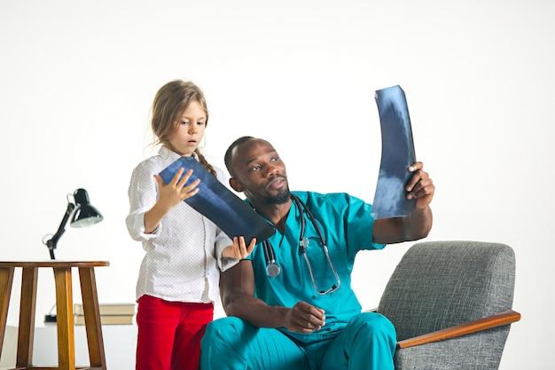 Молодой африканский педиатр мужского пола, объясняющий рентген ребенку Бесплатные Фотографии