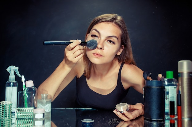 Красота женщина нанесения макияжа. красивая девушка смотрит в зеркало и применяя косметику с большой кистью. Бесплатные Фотографии