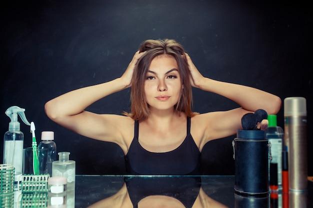 Красота женщины после нанесения макияжа. красивая девушка смотрит в зеркало и применяя косметику с помощью кисти. Бесплатные Фотографии