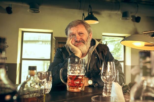 パブでビールを飲んで悲しいシニアひげを生やした男性 無料写真