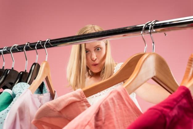 Молодая несчастная симпатичная девушка смотрит на платья и примеряет их, выбирая в магазине Бесплатные Фотографии