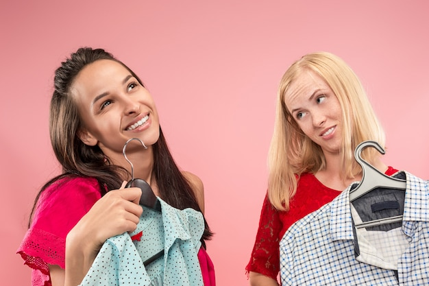 Две молодые красивые девушки смотрят на платья и примеряют их, выбирая в магазине Бесплатные Фотографии