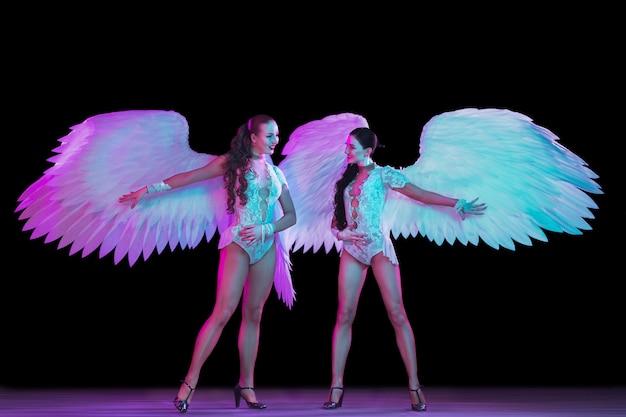 黒い壁にネオンの光で天使の翼を持つ若い女性ダンサー 無料写真