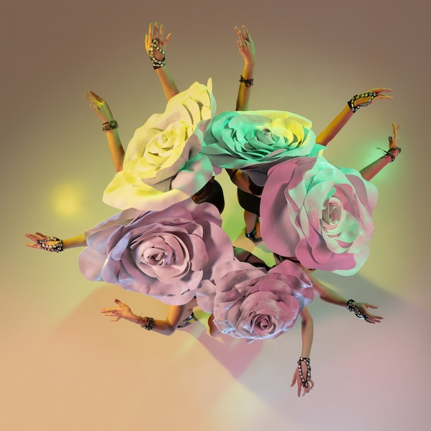 グラデーションの壁にネオンの光で巨大な花の帽子を持つ若い女性ダンサー 無料写真