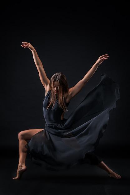 黒い壁の上で踊ってベージュのドレスの若い美しいダンサー 無料写真