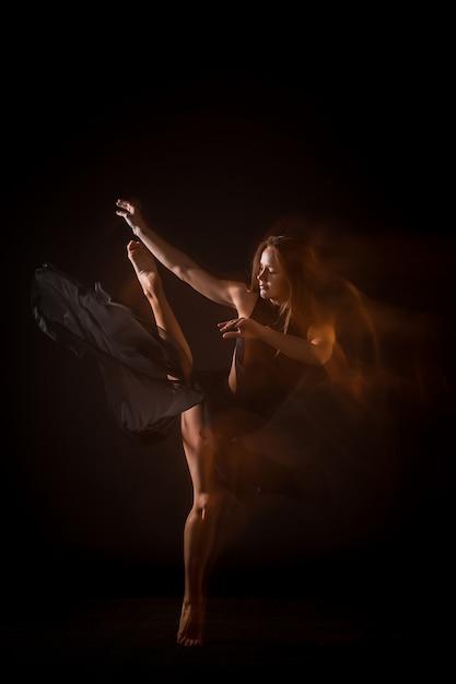 黒い壁の上で踊って若い美しいダンサー 無料写真