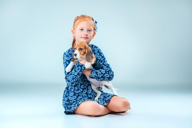 Счастливая девушка и щенок бигля на серой стене Бесплатные Фотографии