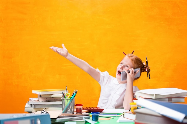 家にたくさんの本を持つ赤毛の十代の少女。 無料写真
